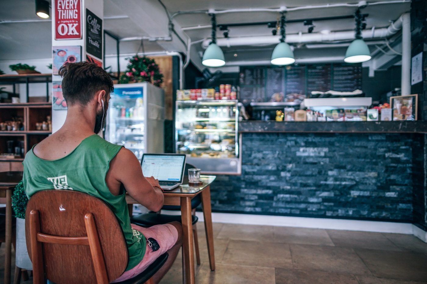 Man sitting in a pizzeria working on his laptop
