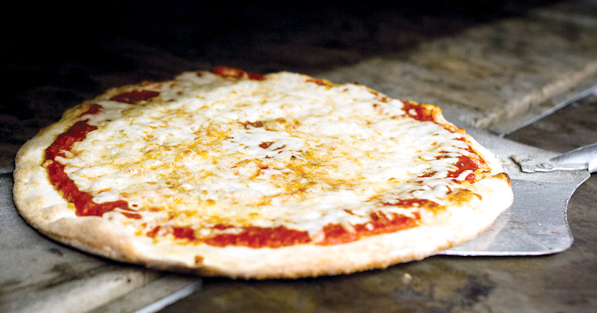 Pizza being pulled out of an oven