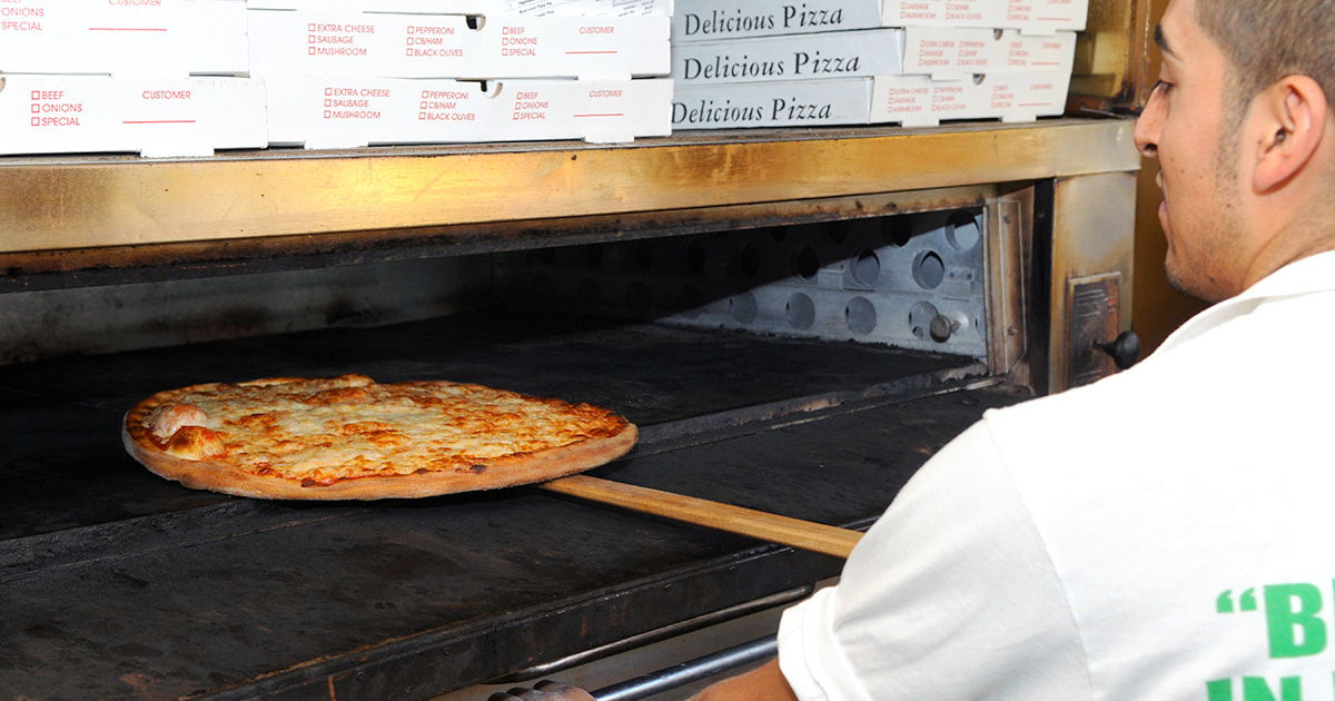 Pizza maker taking fresh pizza out of the oven