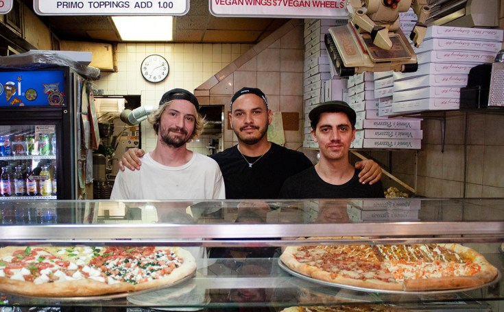 Three guys behind a counter at a pizzeria.