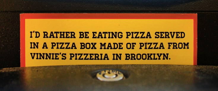 "A sign that says ""I'd rather be eating pizza served in a pizza box made of pizza from Vinnie's Pizzeria in Brooklyn."""