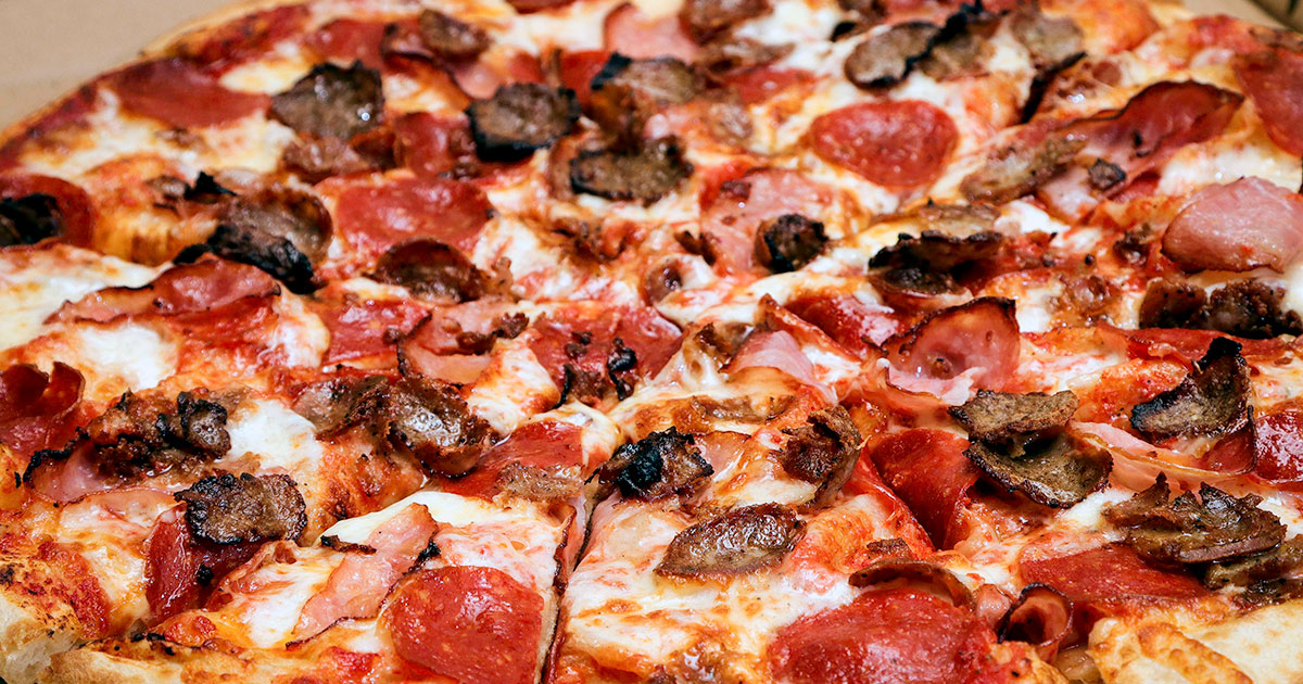 A close up shot of a pizza covered with sausage, pepperoni, and canadian bacon.