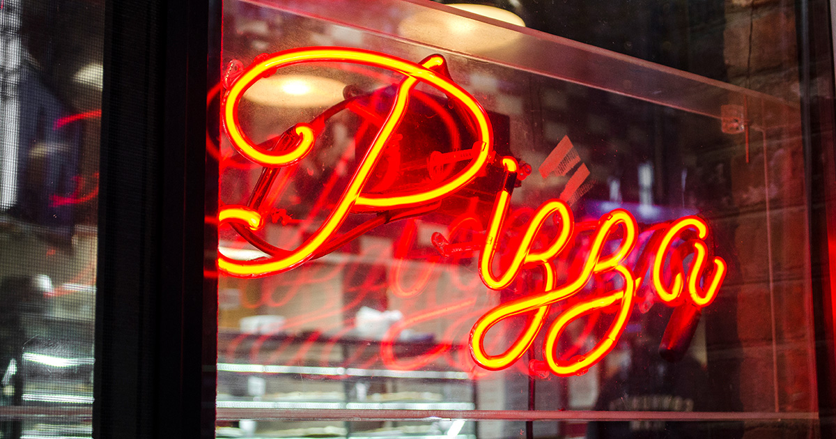 """Orange neon sign hanging in a storefront that reads """"pizza."""""""