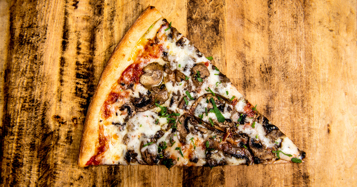 A slice topped with mushrooms on a wooden countertop