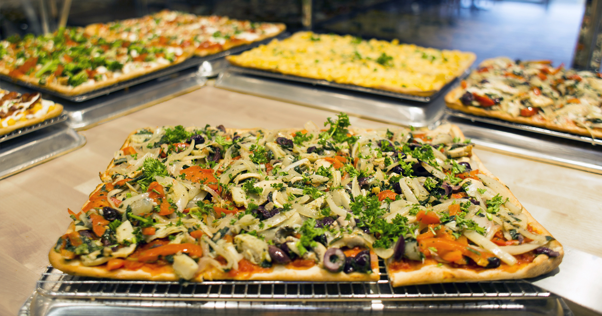 A vegetable-topped pizza sitting on a countertop with six pizzas in the background.