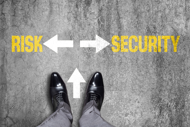 Low section view of a businessman standing by text Risk or Security with opposite arrow signs.