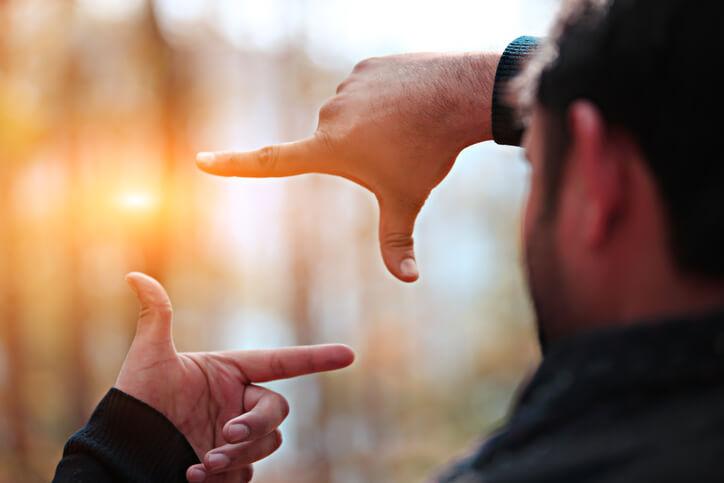 Man hands framing distant sun rays.