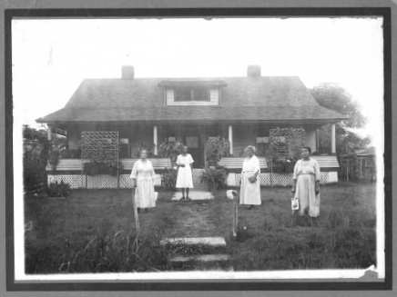 Four women in white dresses stand in the yard of a well-appointed home in North Dallas. One holds a fan.