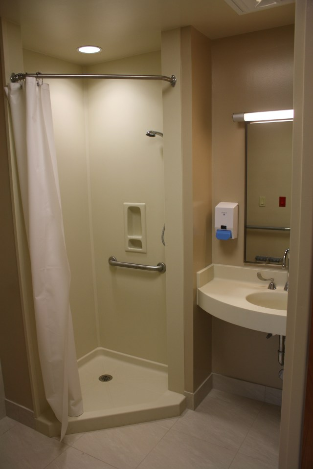 Avonite Surfaces® Bone 8010 shower wet wall panels in a hospital bathroom.