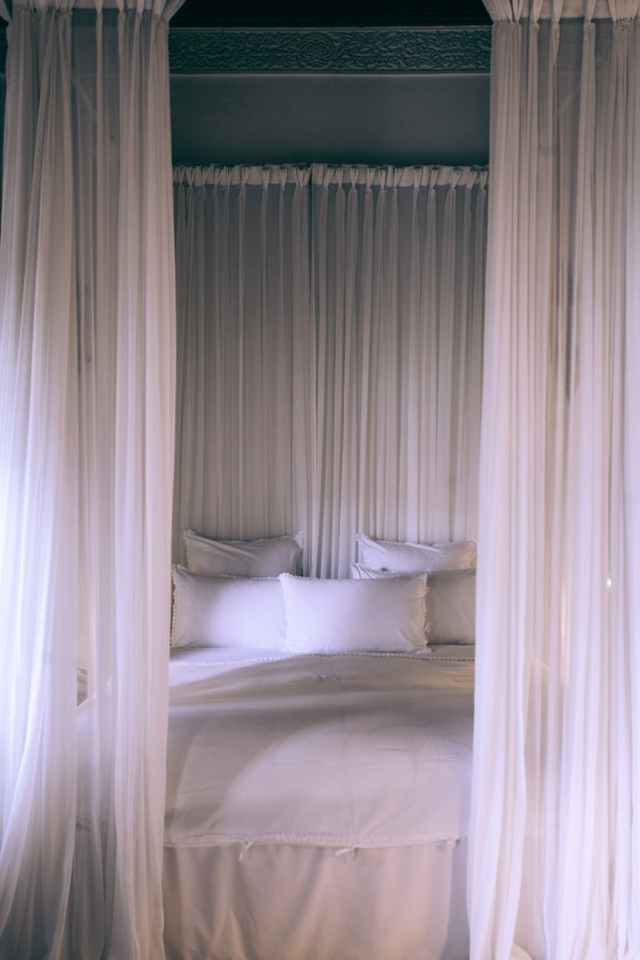 cozy bed under white translucent canopy