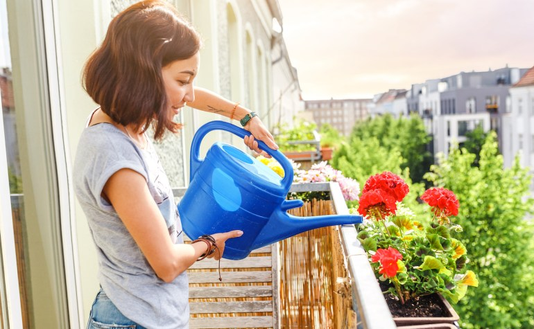 Woman watering plants on balcony