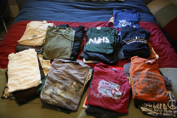 42 T-shirts on a bed