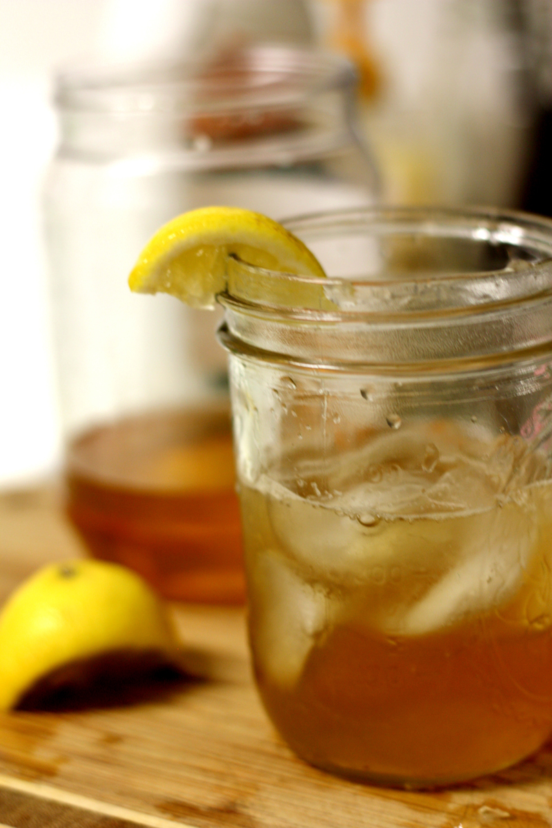 A cocktail in a Mason jar, with a slice of lemon on the rim.
