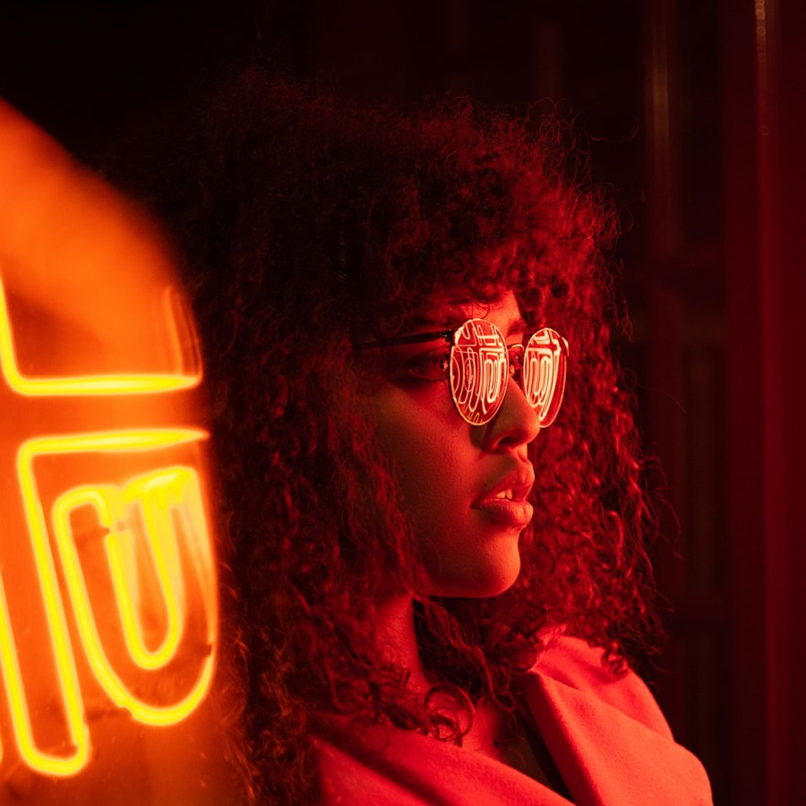 Person with dark, frizzy, wavy hair and round glasses looks to the right. The scene is lit by bright red neon