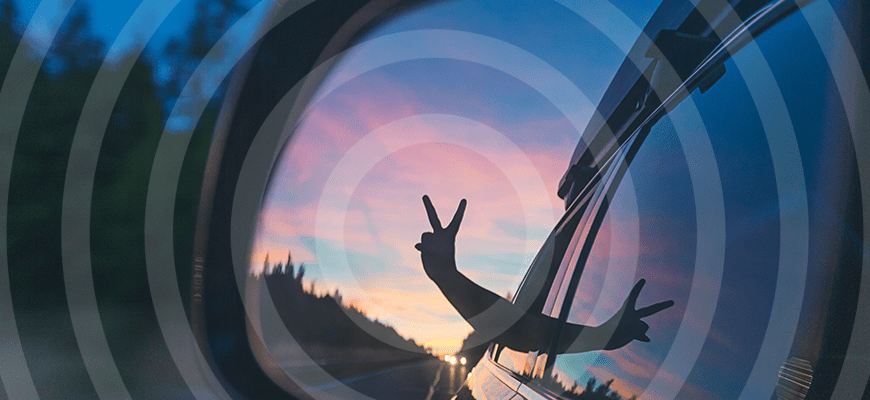 child giving peace sign out car window at sunset