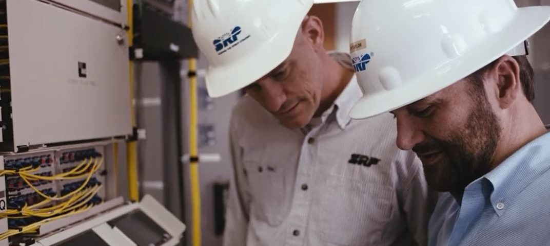 Two employees discussing a telecommunications project in a workroom.