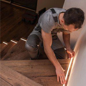 homem instalando fita de led na escada