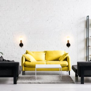 sala com sofá amarelo e arandelas decorativas