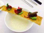 Gemüseveloute mit Brotchip, getrockneten Tomaten, Erbsencreme und Oliven