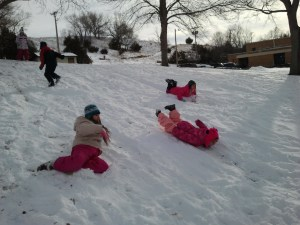 Native American youth sledding down a hill.