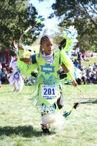 Lakota boy dances fancy dance in the powwow.