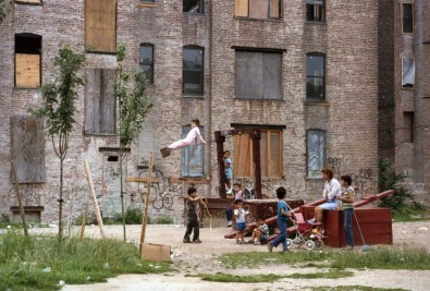 Photo: Mothers and Children Playing in Courtyard of a Boarded-Up Building