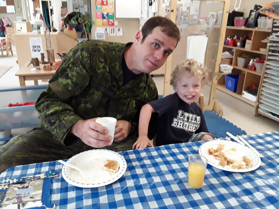 Military father eats with his son