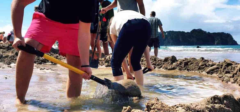 Stray New Zealand travellers digging at Hot Water Beach, Coromandel.