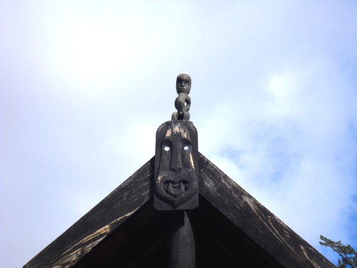 Tekoteko (figurehead on a meeting house) and koruru (carved face representing ancestor after which the house is named) at the Te Hana Te Ao Marama Māori Cultural Centre