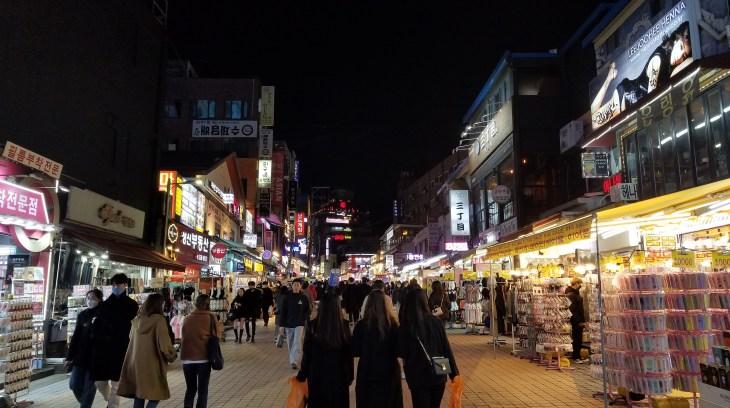 Nightime scene on seoul street. Crowds of people walking past storefronts