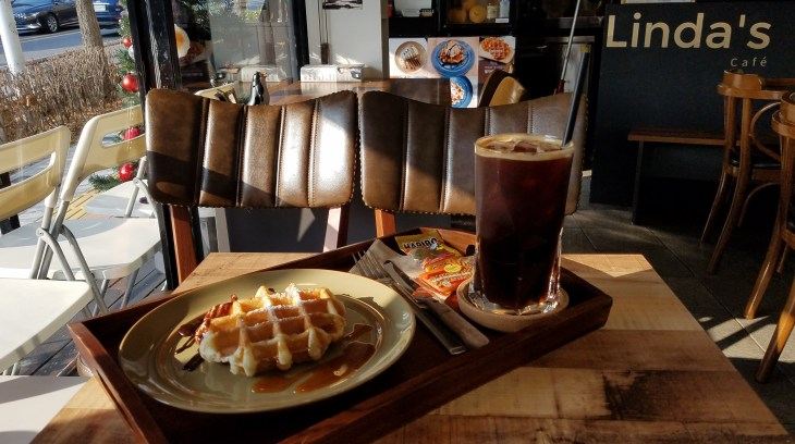Coffee drink and waffle on tray within in a cafe
