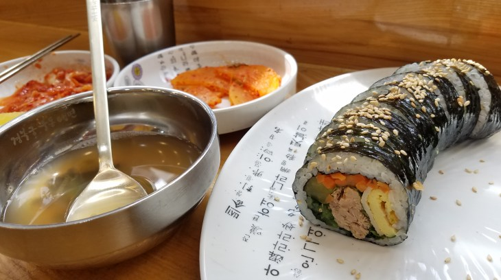 white Plate containing sushi, metal bowl of brith with large spoon