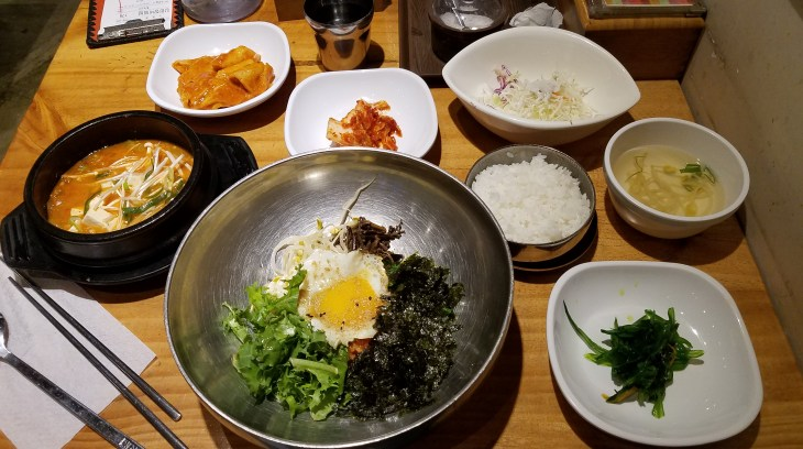 bowl of bibimbap, bowl of soup, surrounded by smaller bowls of assorted toppings