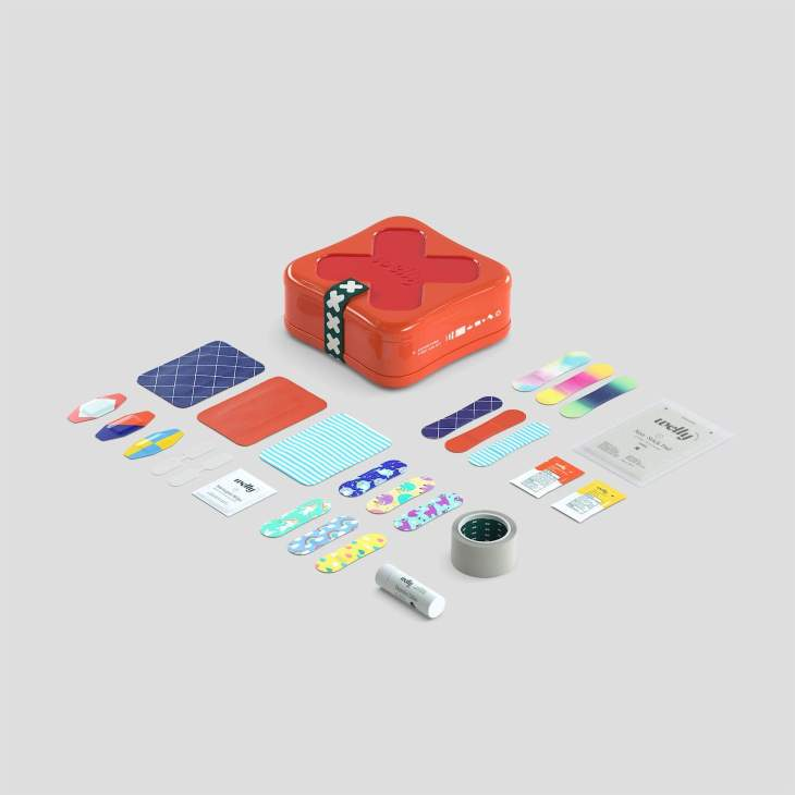 Orange first aid kit box with supplies spread around - bandaids, tape, and ointment