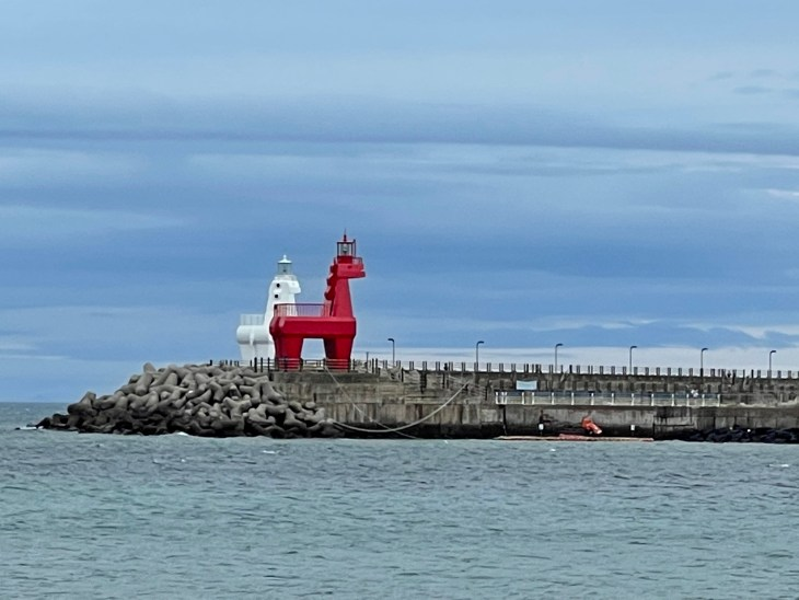 A red and a white horse-shaped lighthouse on Iho Tewoo Beach