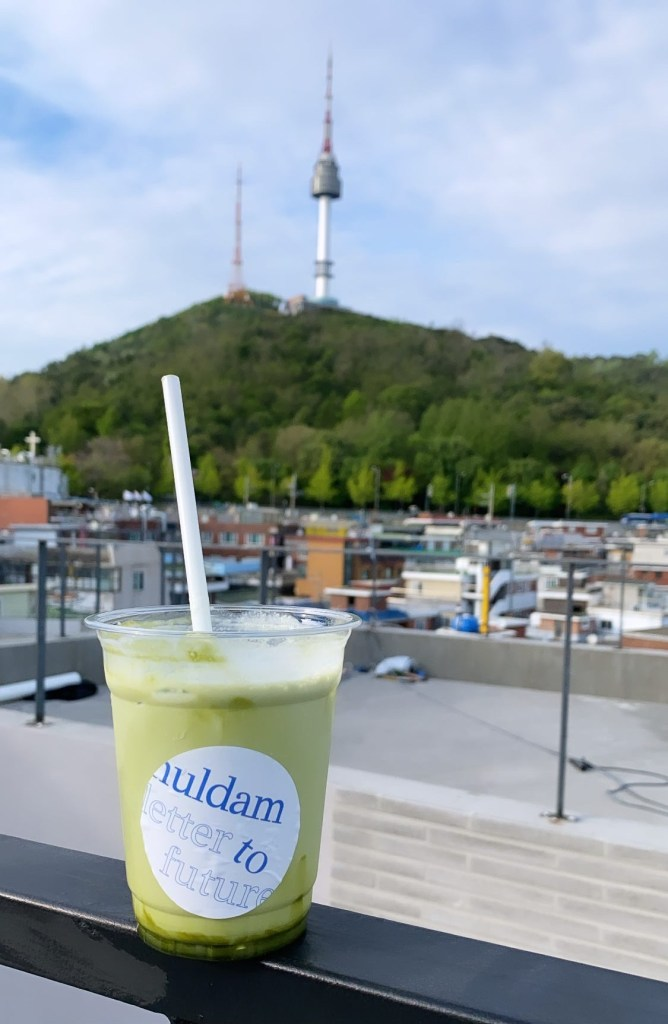 Iced green tea latte in foreground, with seoul tower in the background