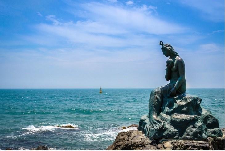 Mermaid statue on rock next to ocean front