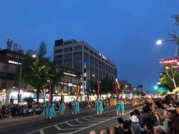 People marching down street in Seoul at night