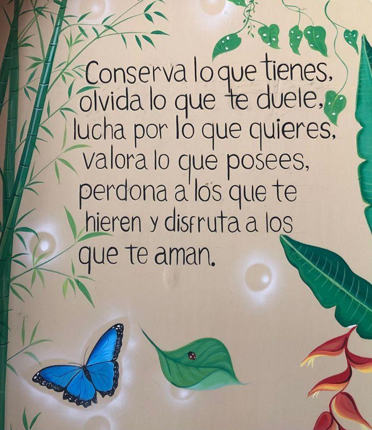 Quote painted on wall: Conserva lo que tienes, olvida lo que te duele, lucha por lo que quieres, valora lo que posees, perdona a los que te hieren y disfruta a los que te aman