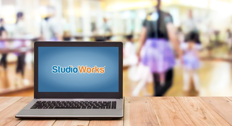 Laptop with StudioWorks logo on a table in front of ballet class