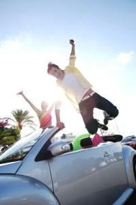 Blije jongeren die juichend uit de auto springen