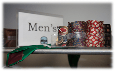 Several rolled up, professional ties for men at the Start Here, Go Far Boutique.