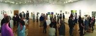art gallery wide view with many people talking in small groups
