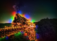 A dark forest landscape with set of train tracks leading out of the forest and off the side of the photo, the tracks and the train on top of them are covered and lit completely by rainbow christmas lights