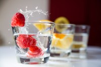 Three glasses of water sit on a table with fruit sitting in them, the closest glass has a raspberry splashing into the water in the glass.