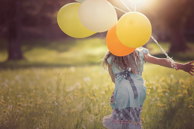Girl running through sunlit field with balloons