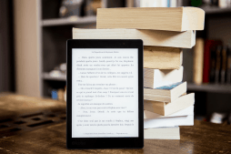 tablet with ebook in front of stack of print books