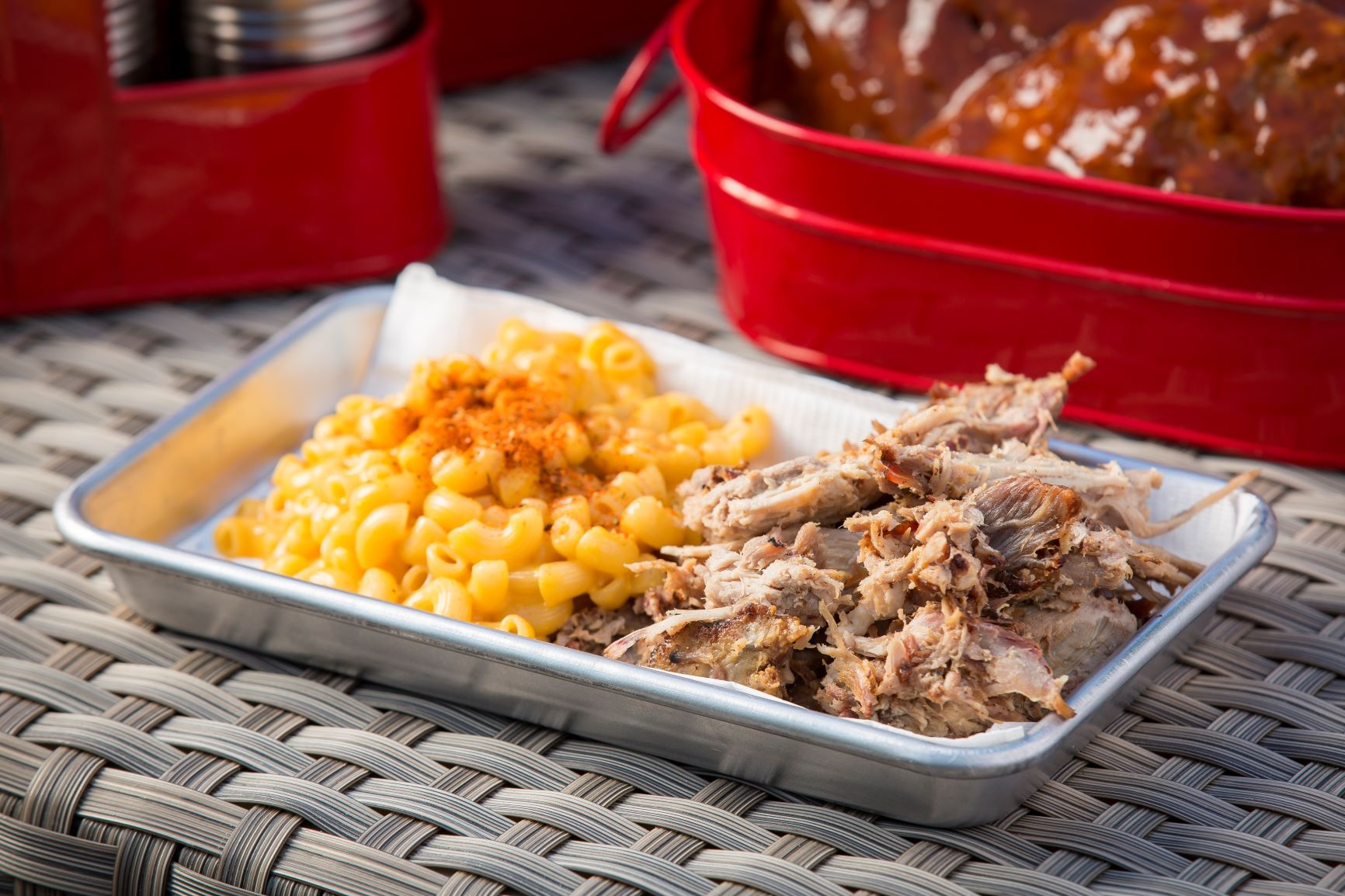 pulled chicken and mac and cheese on a stainless steel server