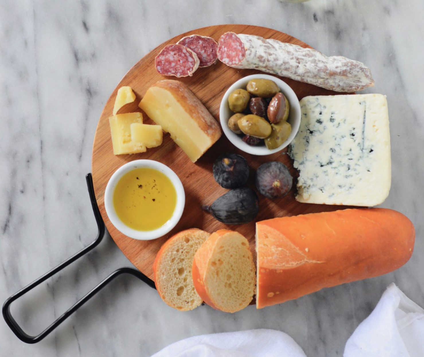 Round board of cheese, meat, olives and bread