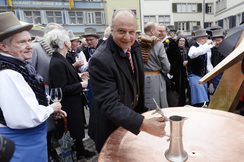 FDP-Stadtrat Filippo Leutenegger wartet auf den goldenen Tropfen bei der Einweihung des Brunnens auf dem Münsterhof, aus dema uch Wein fliessen kann. (Foto: Walter Bieri/Keystone) Zum Artikel